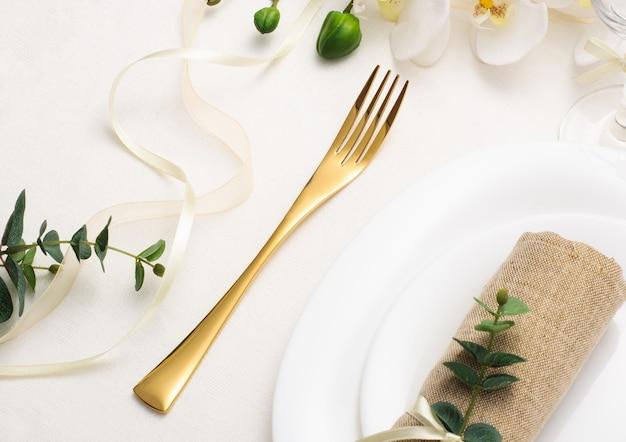 Stół weselny z białymi naczyniami, złotymi sztućcami i kwiatami na białym obrusie, świąteczny stół