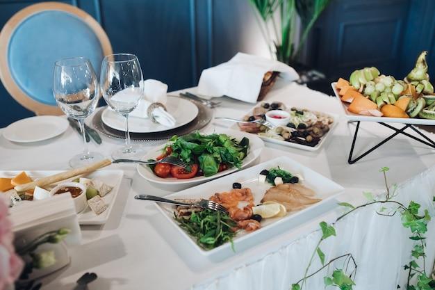 Stół weselny z przystawkami. stół weselny z białym obrusem podany ze zdrową zieleniną, półmiskiem zimnych ryb, półmiskiem serów i półmiskiem owoców.