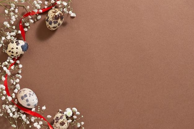 Stół wielkanocny w stylu minimalizmu z pięknymi białymi wiosennymi kwiatami, jajkami przepiórczymi i czerwoną wstążką
