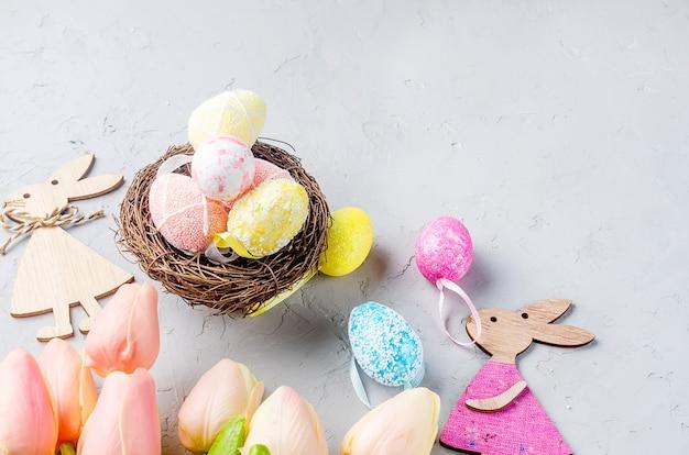 Stół wielkanocny z kolorowymi ozdobnymi jajkami w gnieździe i tulipanami