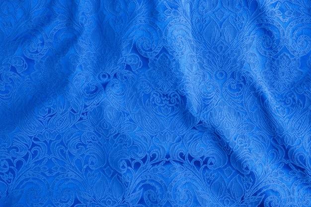 Stół wykonany jest z niebieskiego materiału tekstylnego abstrakcyjny rysunek gobelinu, faktura elementu ubioru.