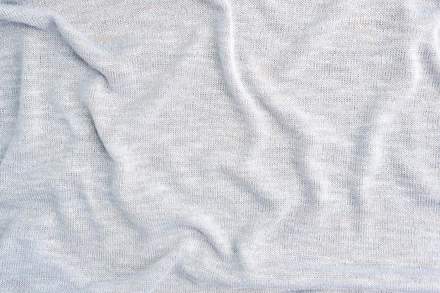 Stół wykonany jest z szarego materiału tekstylnego o fakturze ubrania.