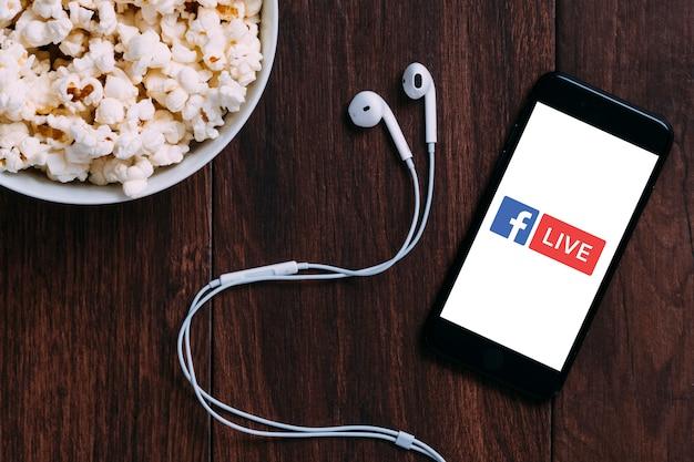Stół z butelką popcornu i logo facebook na żywo na apple iphone i słuchawkach.