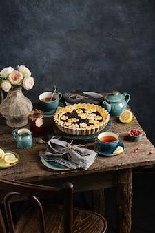 Stół z ciepłym ciastem jagodowym, gorącymi filiżankami z herbatą cytrynową, dżemem i kwiatami