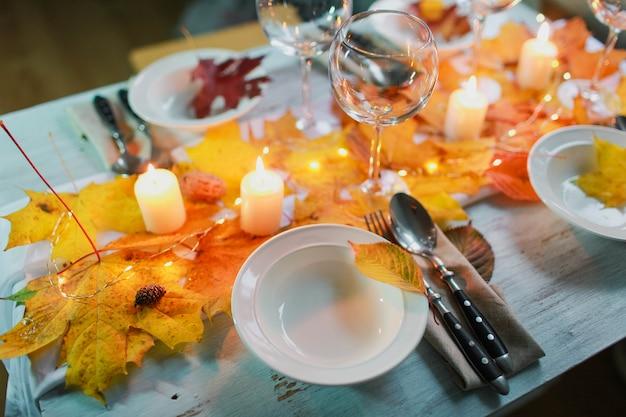 Stół z dekoracjami, świecami i jesiennymi liśćmi