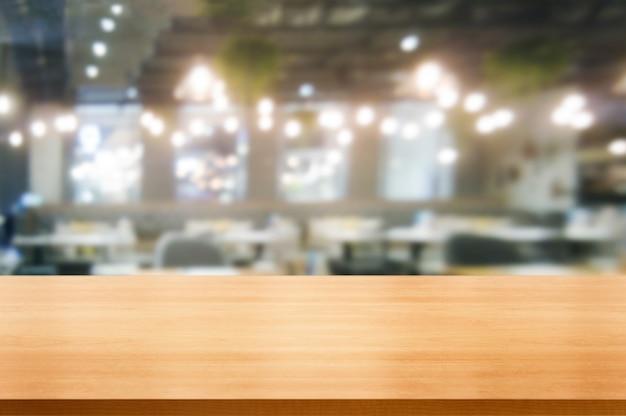 Stół z drewna w rozmytym tle nowoczesnej sali restauracyjnej lub kawiarni do makiety wyświetlania produktu.