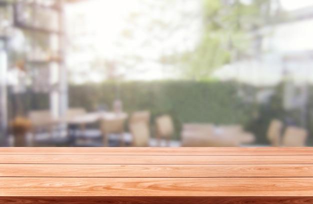 Stół z drewna w rozmytym tle nowoczesnej sali restauracyjnej lub kawiarni do wyświetlania produktów