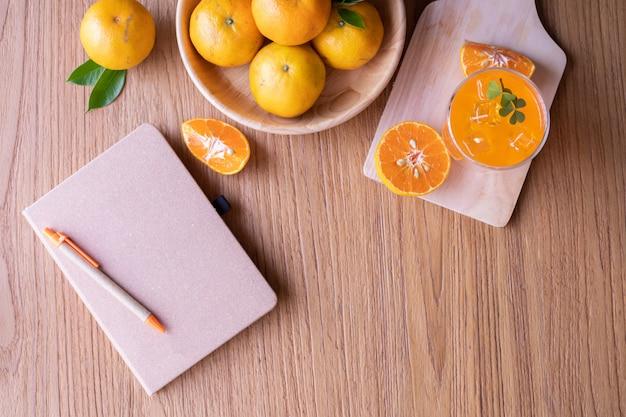 Stół z drewna z kubek zimny sok pomarańczowy i puste okładki książki na stół z drewna.