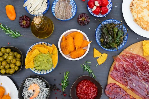 Stół z hiszpańskimi tapas - anchois, padron z zieloną papryką, jamon, krokiety, guacamole