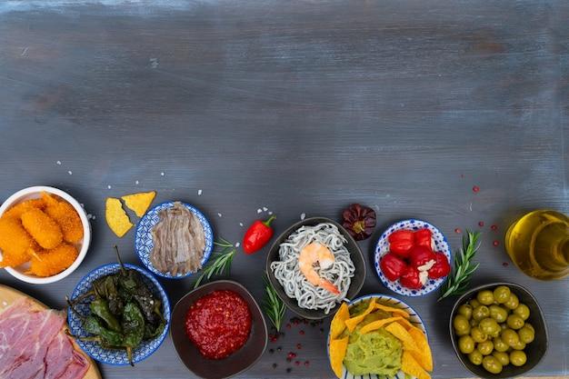 Stół z hiszpańskimi tapas - anchois z papryką padron, jamonem, krokietami, guacamole i oliwkami