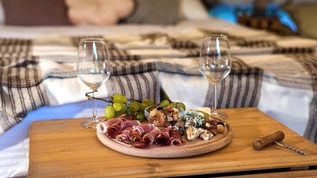Stół z jedzeniem i kieliszkami do wina w namiocie w glampingu