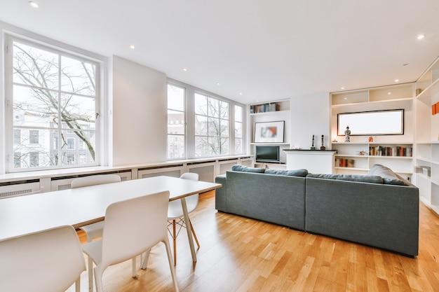 Stół z krzesłami i kanapą ustawione przy regałach z dekoracjami i telewizorem w jasnym pokoju współczesnego mieszkania