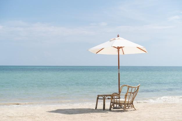 Stół z krzesłami i parasolem ustawiony na romantyczny posiłek na plaży, niebie i morzu w tle.