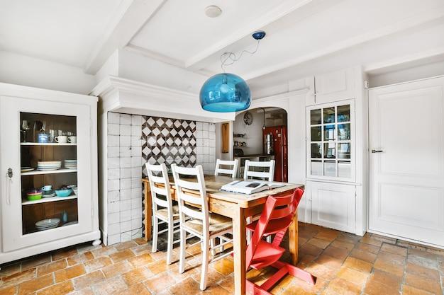 Stół z krzesłami w przestronnej jadalni ze stylowymi dekoracjami w nowoczesnym mieszkaniu