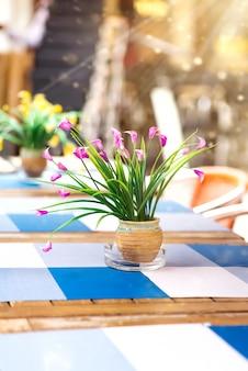Stół z kwiatami i krzesłami w ulicznej kawiarni.