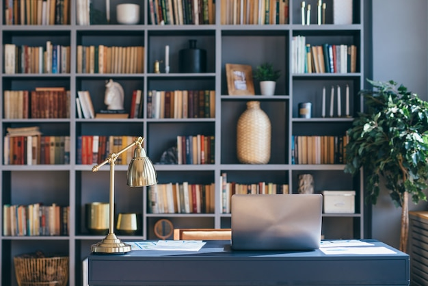 Stół z laptopem we wnętrzu biura domowego.