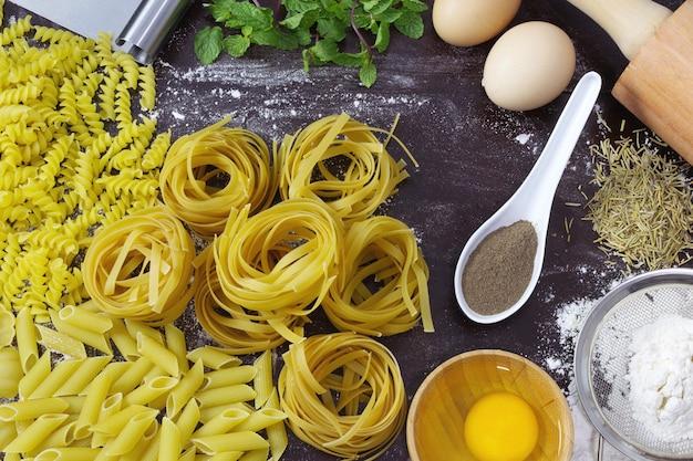 Stół z makaronem i składnikami do ich przygotowania widok z góry