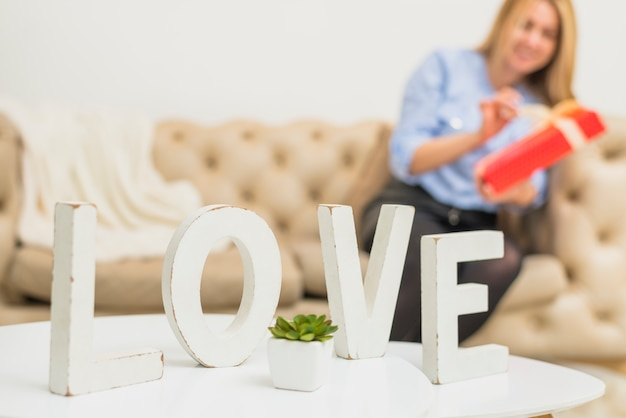 Stół z miłość znakiem blisko młodej damy z prezenta pudełkiem na kanapie
