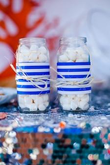 Stół z morskim danierem i talerz ze słodyczami, cukierkami, ciastkami i zdobi słoiki pianką