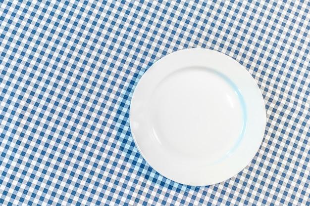 Stół z niebieską tkaniną piknikową i talerzem