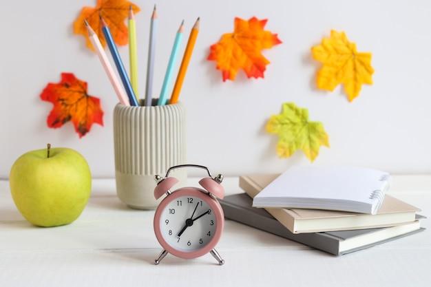 Stół z przyborami szkolnymi budzik zeszyty ołówki i zielone jabłko z powrotem do koncepcji szkoły