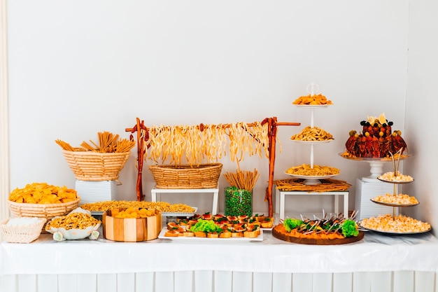 Stół z przystawką na weselu. ser, frytki, orzechy, kraby na stole.