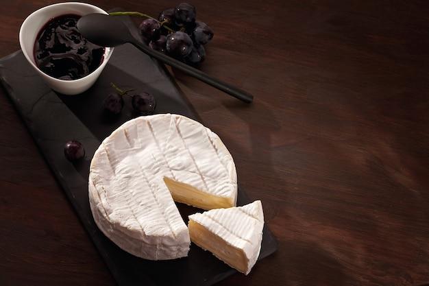 Stół z przystawkami z francuskim serkiem camembert i winogronami na aperitif w formie bufetu