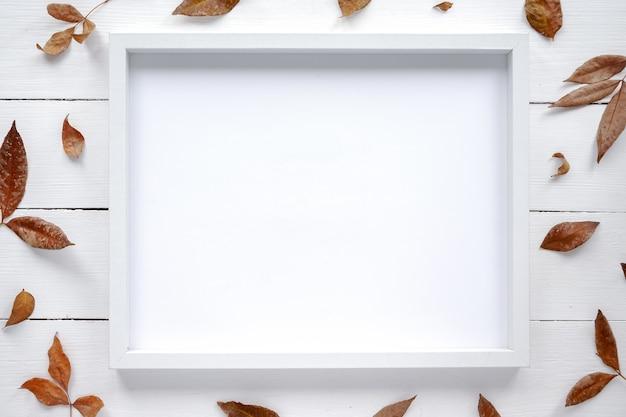 Stół z ramką na zdjęcia i dekoracją z suszonych gałązek. widok z góry
