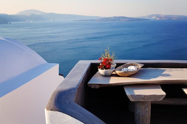 Stół z roślinami i widokiem na morze na wyspie santorini, grecja