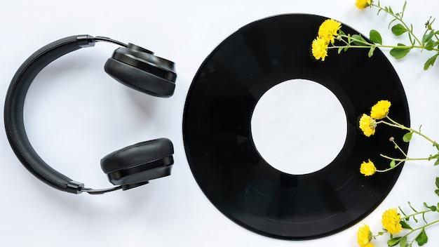 Stół z rzeczami do słuchania muzyki. słuchawki, płyta muzyczna i dekoracja kwiatowa. widok z góry
