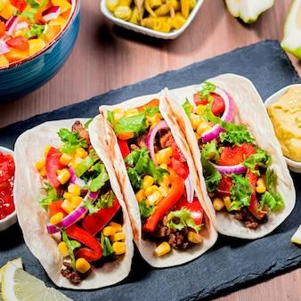 Stół z tacos, salsą mango, nachos z sosem, guacamole, piwem cytrynowym na przyjęcie w cinco de mayo. przystawki i tradycyjne dania meksykańskie na rodzinny obiad na drewnianym stole, miejsce na tekst