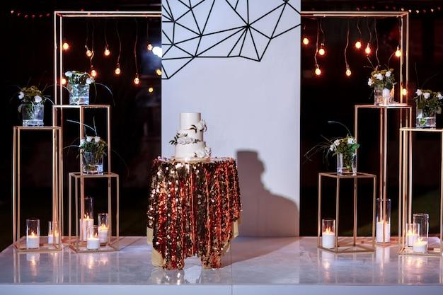 Stół z tortem ślubnym, świecami, światłem i kwiatami. dekoracja ślubna