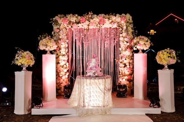 Stół z tortem ślubnym, świecami, światłem i kwiatami.