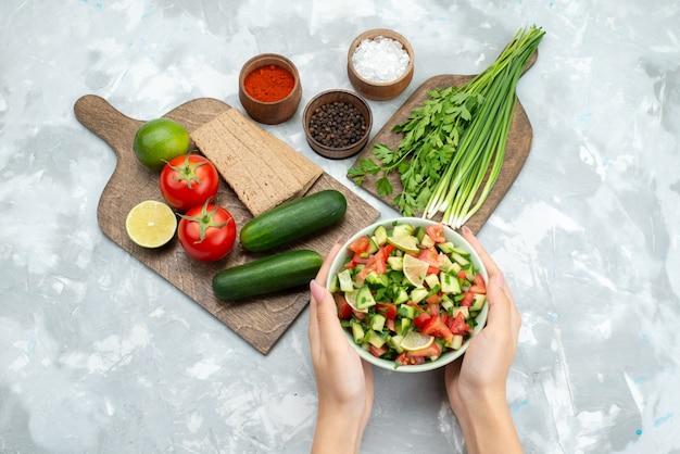 Stół z widokiem z góry z warzywami, takimi jak pomidory, ogórki, a wraz z chipsami cytrynowymi i zieleniną na białym, sałatkowym jedzeniu warzywnym