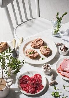 Stół zastawiony kiełbaskami i kanapkami z pasztecikami.