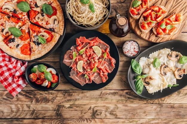 Stół ze smacznymi włoskimi posiłkami na talerzach