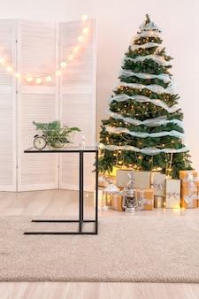 Stół ze świątecznymi dekoracjami i piękną jodłą we wnętrzu salonu