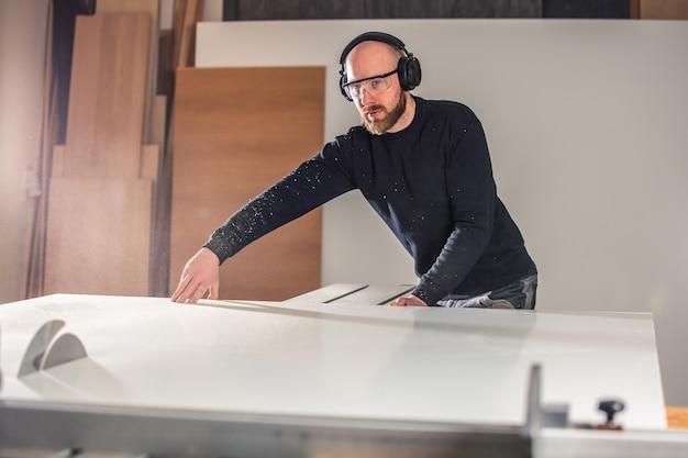 Stolarstwo, stolarstwo i meblarstwo, profesjonalny stolarz docinający drewno w stolarni, koncepcja przemysłowa
