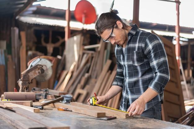 Stolarz człowiek za pomocą drewnianej deski z miarką linijki w warsztacie stolarskim