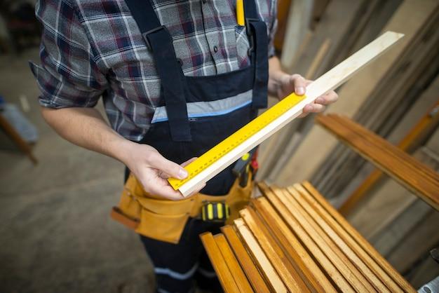 Stolarz dokonujący pomiarów deski, którą ma wyciąć w warsztacie stolarskim