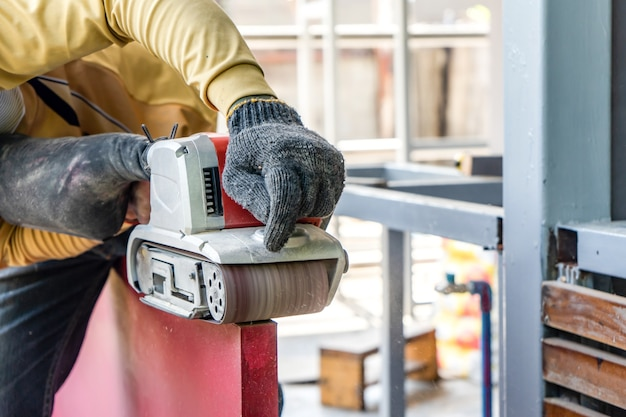 Stolarz goli czerwone drewniane drzwi swoją maszyną do golenia na zewnątrz w otoczeniu konstrukcji stalowego słupa.