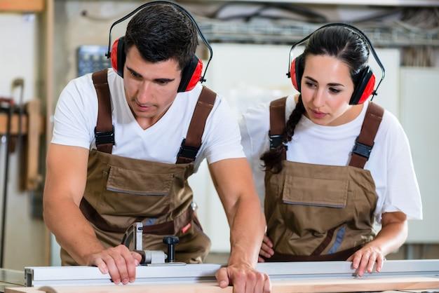 Stolarz i praktykant pracujący razem w warsztacie stolarskim