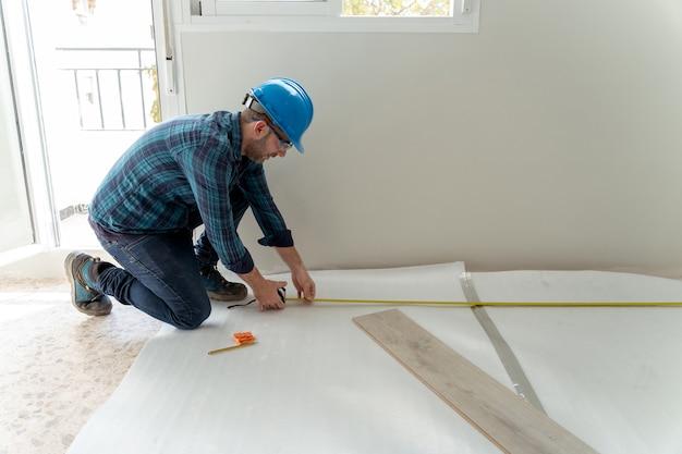 Stolarz instalujący podłogę laminowaną w pokoju.