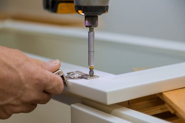 Stolarz instaluje widok ulepszenia zawiasu drzwi szafy i zainstalował nową kuchnię