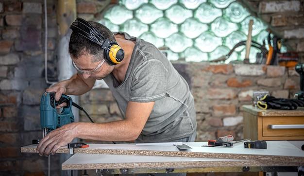 Stolarz kaukaski koncentruje się na cięciu drewna wyrzynarką w swoim warsztacie.