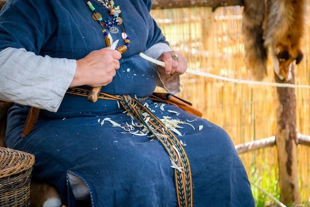 Stolarz kobiety ubrany w wiejską odzież i rzeźbiący drewniany kij