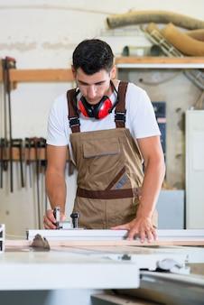 Stolarz lub stolarz w swoim warsztacie stolarskim