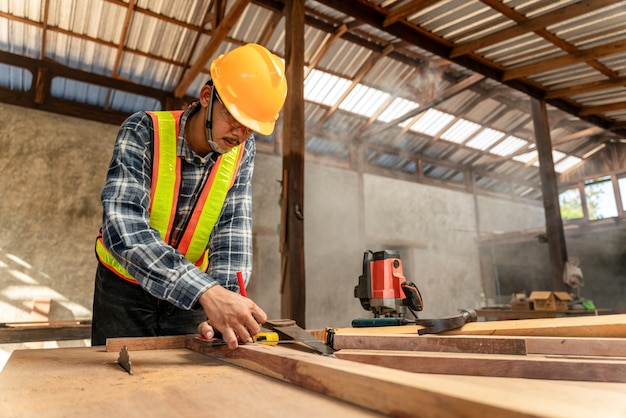 Stolarz mężczyzna używający ołówka na kawałku drewna na budowie