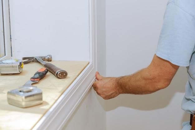 Stolarz montuje do listew na drzwiach, przybija gwoździami do wykończenia obramowania