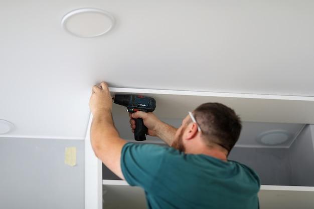 Stolarz montuje meble w domu za pomocą śrubokręta zbliżenie mężczyzna mocuje półkę do ściany